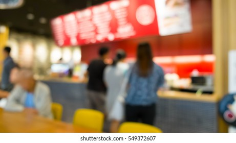 Blur of coffee shop and customer standing in the line for waiting order in front of counter/ Food center, use for background