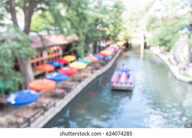 Blur colorful River Walk in downtown San Antonio, Texas, US. Multicolor umbrella of cafe, restaurant.  Tourists enjoy riding boat tour, narrative guide along famous, historic destination. Vintage tone
