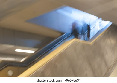 Blur of couple descending escalator from blue-lit space into cream and grey duller level