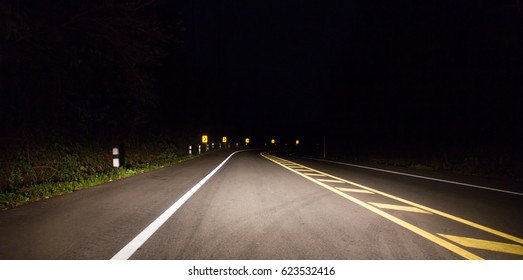 Blur of dark road in the forest.