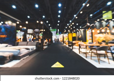 Blur, defocused background of public exhibition hall holding furniture fair event or business tradeshow. Commercial trading convention center, interior design expo, or shopping mall marketing concept