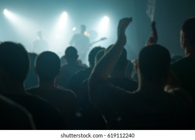 Blur defocused concert crowd fans as abstract background, people at popular rock music live performance, hands in the air
