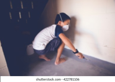 Blur defocused photo of a boy helping painting floor with brush, selective focus, toning