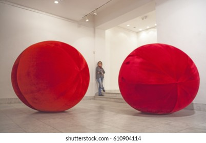 Blur of figure with two big, red, plush balls