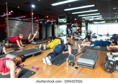 Blur Fitness class with group of people excercising with barbell, dumbbell