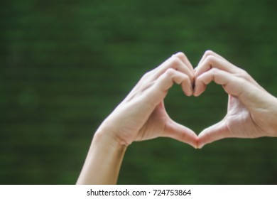 Blur focus Heart shaped symbolizes love,compassion and friendship Patterns and gestures of hands on a dark green background blur.