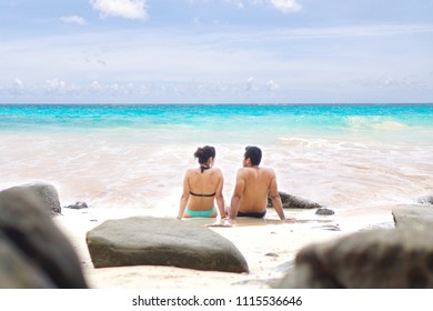 Blur Focus of romantic couple in love sitting together on the tropical beach.Man and woman in holidays with relaxing time on paradise beach.Travel,Vacation,Honeymoon,Summer Concept.