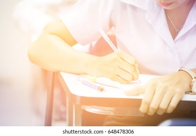 blur focus undergraduate student holding pencil and sitting on row chair doing final exam attending in examination room or classroom.university student in uniform.