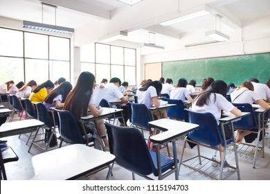 blur focus.back view abstract background of examination room with undergraduate students inside. university student in uniform sitting on lecture chair taking final exam or study in classroom.