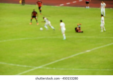 Blur of football players running on the field during match.
