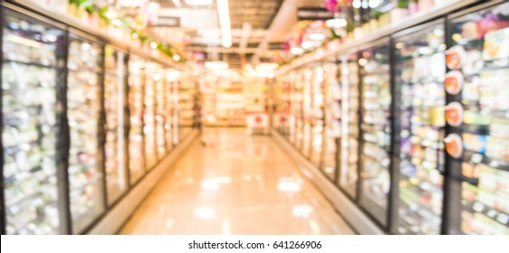 Blur frozen food section at retail store in US. Huge glass door aisle with variety pack processed fruit, vegetable, breakfast, appetizer, side, meals , pizza , produce, meat and seafood.Panorama style