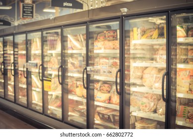 Blur frozen food section at retail store in America. Huge glass door aisle with variety pack of processed pizza. Freezer full assortment of frozen pizza in local supermarket background. Vintage tone.