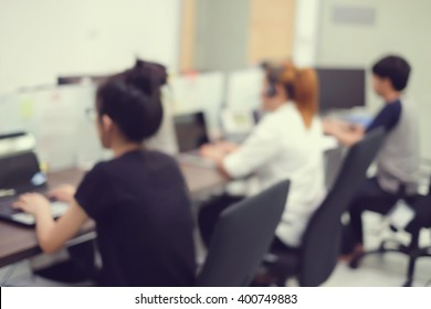 blur group of asian staff working in operation office room for customer support service concept.