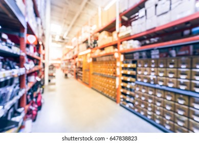 Blur hardware store in America. Defocused home improvement retailer with rack of drywall tools, join compound, rebar, deck boards, stair parts, wet/dry vacuums, tool boxes, child safety. Vintage tone.