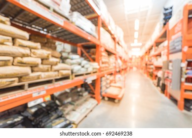 Blur hardware store with flatbed cart in US. Defocused interior home improvement retailer, rack of Concrete, Cement & Masonry material, tools, accessories from floor to ceiling. Inventory, wholesale