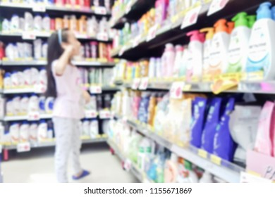 Blur image of Asian kid choose shampoo by her self.