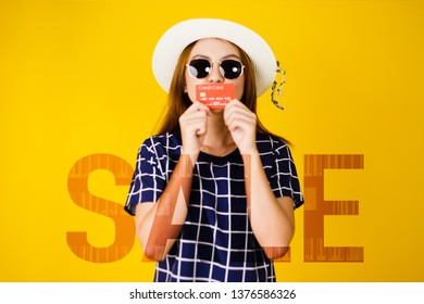 Blur image of Asian young woman portrait in sunglasses holding and kiss credit card with Sale text, Double Exposure, Shopping mid-year sale concept isolated on yellow background.