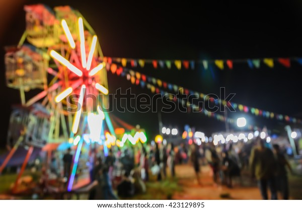 Blur image background of asian travelling funfair with portable ferris wheel