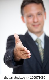 Blur image of a business executive offering you a handshake