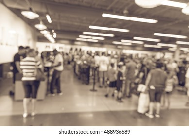 Blur image cashier with long line of people waiting at checkout counter in fitness store at outlet shopping mall in Houston, Texas, US. Cashier register and payment concept background. Vintage filter.