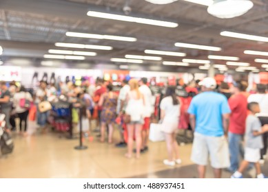 Blur image cashier with long line of people waiting at checkout counter in fitness store at outlet shopping mall in Houston, Texas, US. Cashier register and checkout payment concept background.