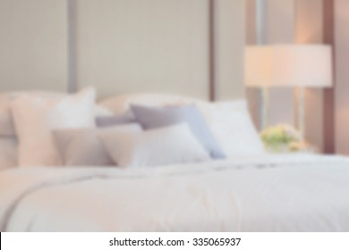 blur image of classic bedroom interior with pillows and reading lamp on bedside table