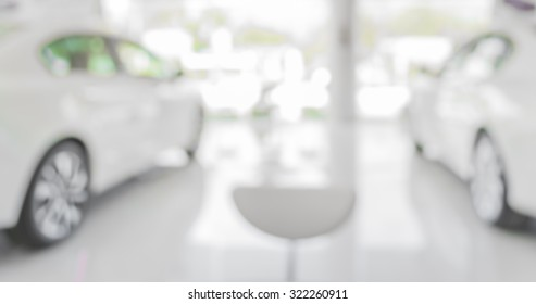 blur image of Commercially cars stand in show room of car shop for background usage.