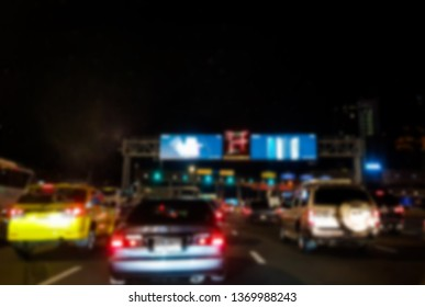 Blur image concept of Toll booth on hight way in night time and traffic jam concept in side car