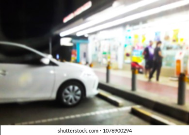 Blur image of the in front of the convenience store at night.