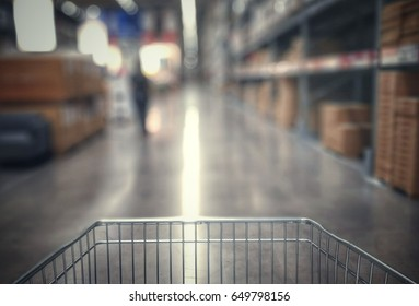 Blur image of front part shopping cart move foward in warehouse or sale floor area, effected by vintage or classic style.