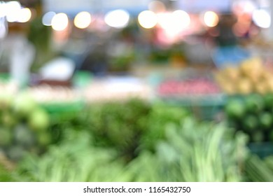 blur image of fruits and vegetables in the local market - unrecognized people shopping - blurred background concept