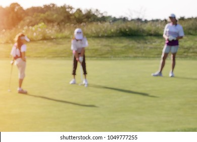 BLUR IMAGE OF A GIRL JUNIOR GOLFER PUTTING A GOLF BALL ON THE GREEN IN BEAUTIFUL SUNSET LIGHT