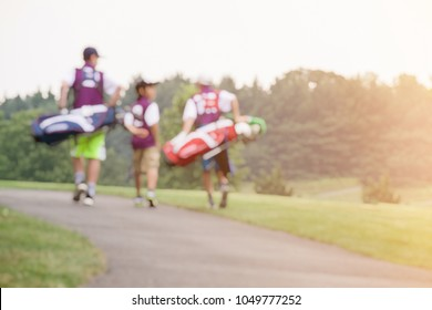 BLUR IMAGE OF A GROUP OF BOY JUNIOR GOLFERS CARRYING GOLF BAGS WHILE WALKING ON CART PATH IN A GOLF COURSE WITH BEAUTIFUL SUNSET LIGHT