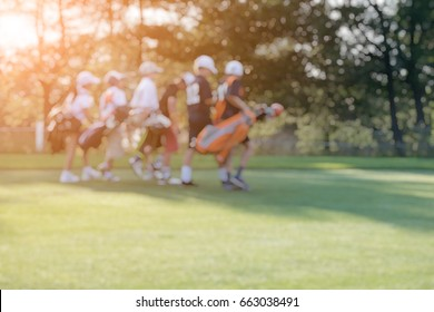 BLUR IMAGE OF A GROUP OF JUNIOR GOLFERS CARRYING GOLF BAGS WHILE WALKING ON A FAIRWAY IN A GOLF COURSE WITH BEAUTIFUL SUNSET LIGHT