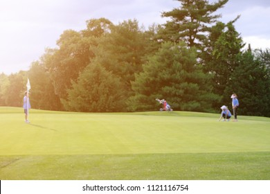 Blur image of a junior girl setting golf ball on green while a boy standing at a flag in beautiful sunset light.