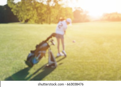 BLUR IMAGE OF A JUNIOR GOLFER (GIRL) HITTING A GOLF BALL WITH FAIRWAY WOOD IN BEAUTIFUL SUNSET LIGHT