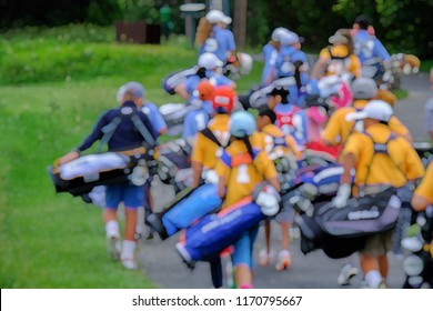 Blur image of junior golfers carrying golf bags while walking on path in a golf course.