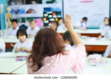 Blur image of Kids raising hands to answer in an elementary school class.