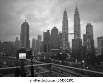 Blur image of Kuala Lumpur cityscape in black and white with a photographer dslr camera on a sturdy tripod.taking photo for stock photo