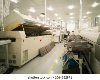 blur image of Machine SMT open cover each separate table  weekly maintenance at surface Mount Technology (SMT) for manufacturing of electronic equipment, blur background
