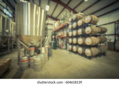 Blur image modern beer plant (brewery), stainless steel brewing equipments and stack of barrels in cellar. Row large tanks in microbrewery. Brewery production vats, fermentation interior. Vintage tone