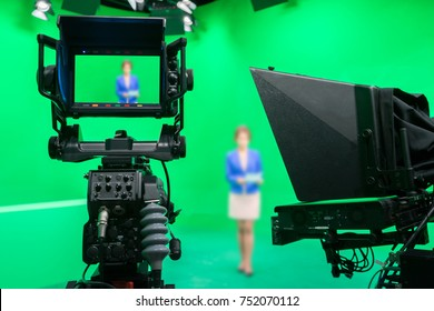 Blur image of newscaster or announcer preparing to record program in broadcast television virtual greenscreen studio room with professional cameras.