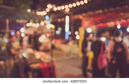 blur image of night festival on street blurred background with bokeh . (vintage tone)