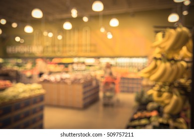 Blur image of organic fresh produces, fruits, vegetable on shelves in store  at Houston, Texas, US. Blurred grocery store with customer with bokeh light background. Healthy concept. Vintage filter.