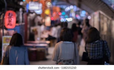 Blur image of pedestrian walking under the railway track bridge tunnel  in  Yurakucho district at night.