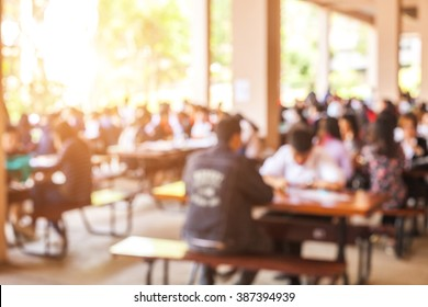 blur image of People eating cafeteria in the University and sun light