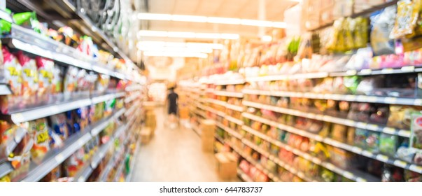 Blur image of rice snacks, Korean & Japanese snacks, canned chips, and nut on shelves in Asian grocery store at Houston, Texas, US. Defocused background bokeh light of rows and aisles. Vintage tone.