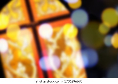 Blur image of stained glass church window in orange or red tone color with bokeh