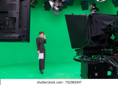 Blur image of television announcer in broadcast green screen studio room with professional camera and LED lights on the ceiling.