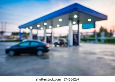 Blur image of twilight gas station at sunset.